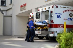 Two paramedics loading a patient into an ambulance.