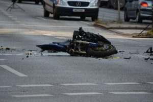 Damaged motorcycle laying in the street after an accident.